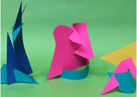 Three paper sculptures standing up, they are different colors and look like someone cut shapes out of paper, folded/rolled them and then stacked them up.