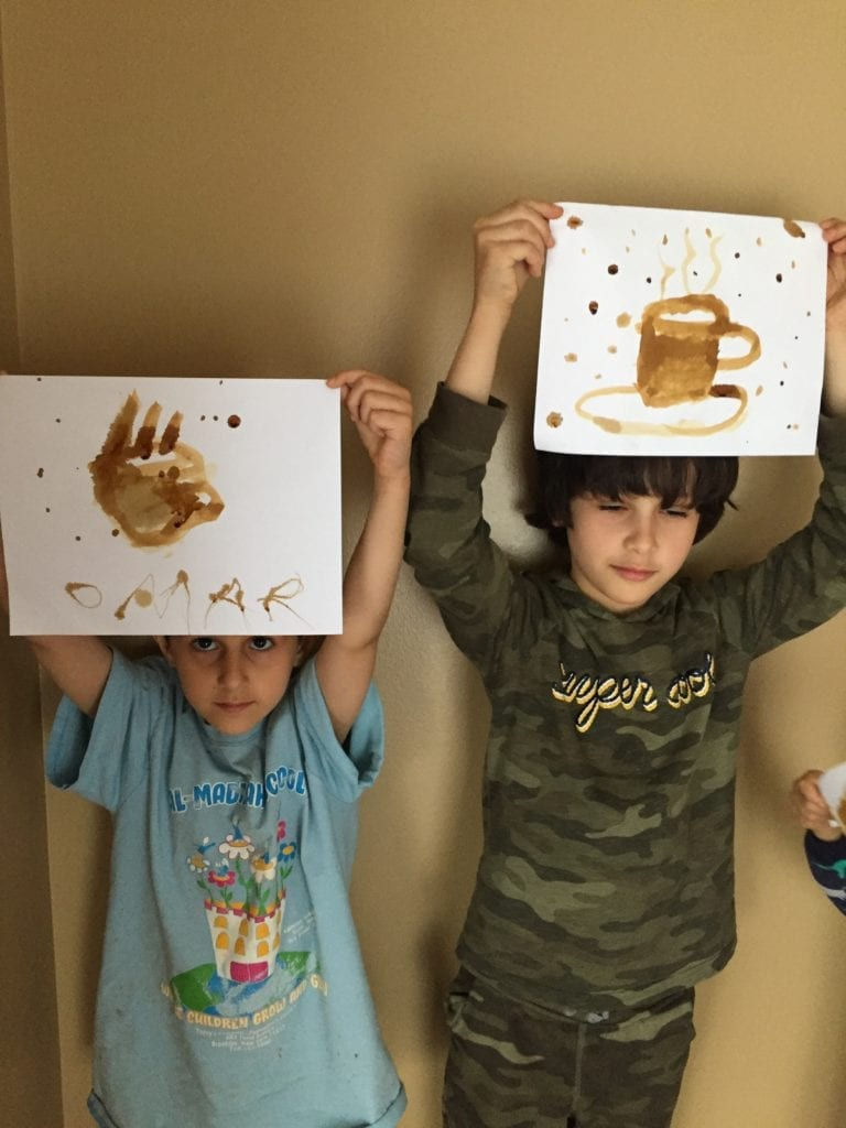 two boys holding up painting of coffee made with coffee