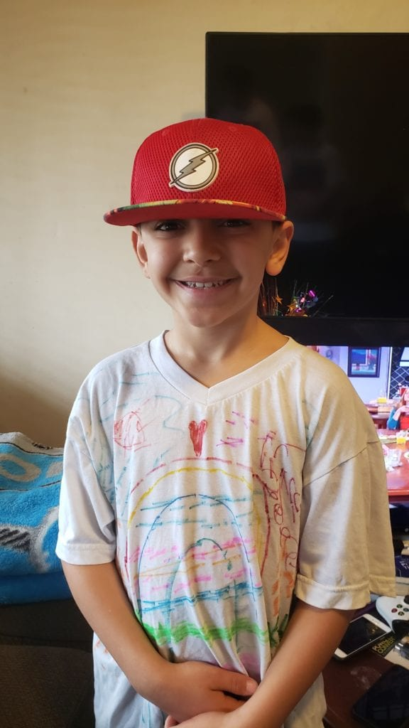 Boy wearing a red hat and a shirt that he drew designs of a rainbow and a heart on