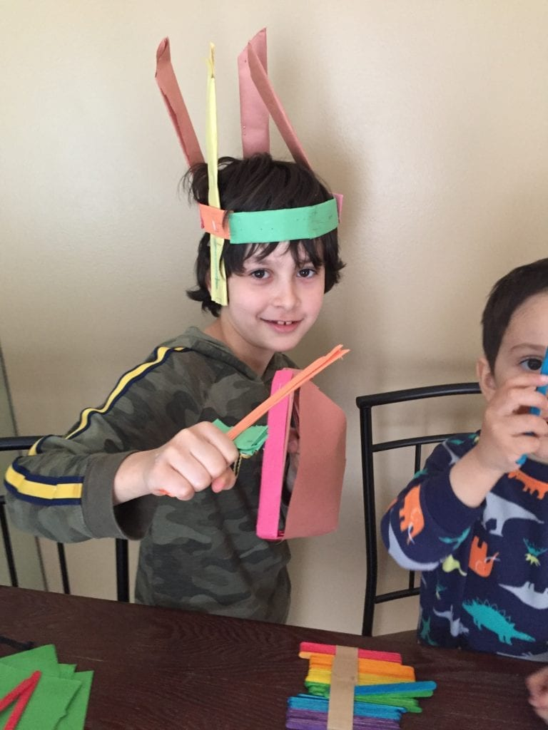 boy wearing paper headband and holding paper objects he made