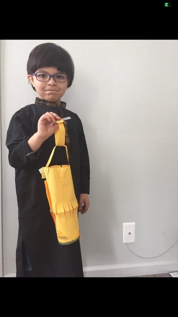 a boy holding a yellow paper lantern