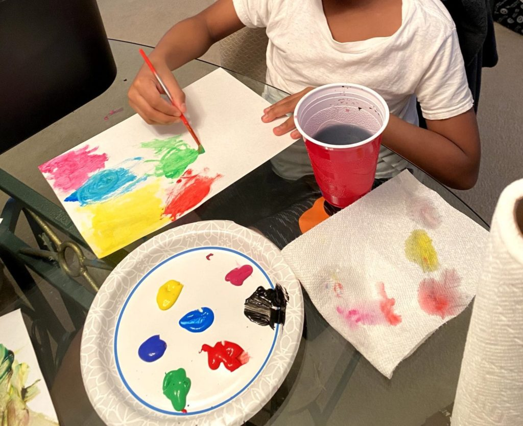 boy painting with colors on a paper