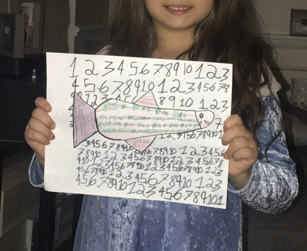 girl holding a ptterned fish with numbers all around the fish