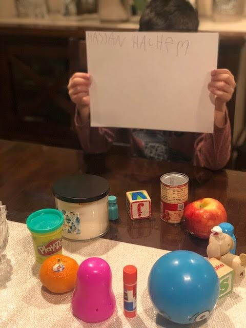 a circle of colorful objects (orange, playdough, gluestick apple, etc.) on a table with a boy holding up a paper with his name on it in front of his face