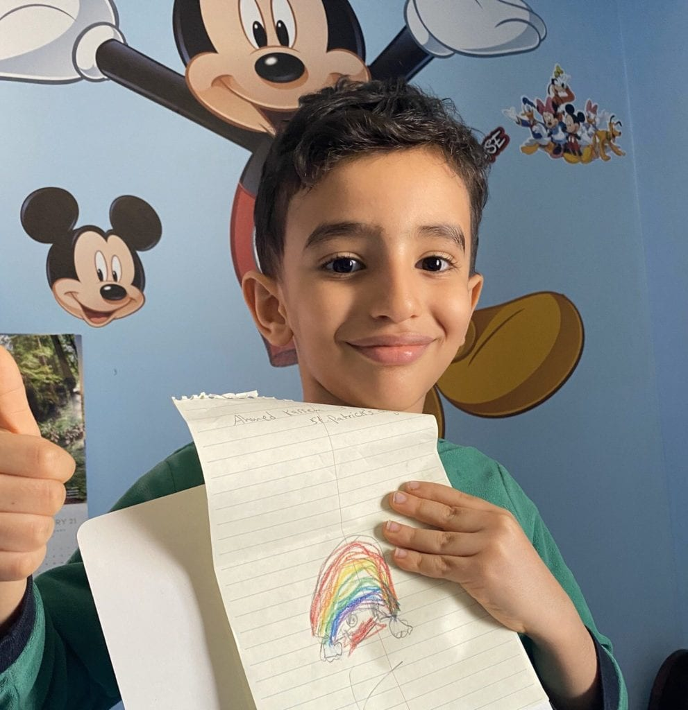 boy smiling holding a drawing of a rainbow