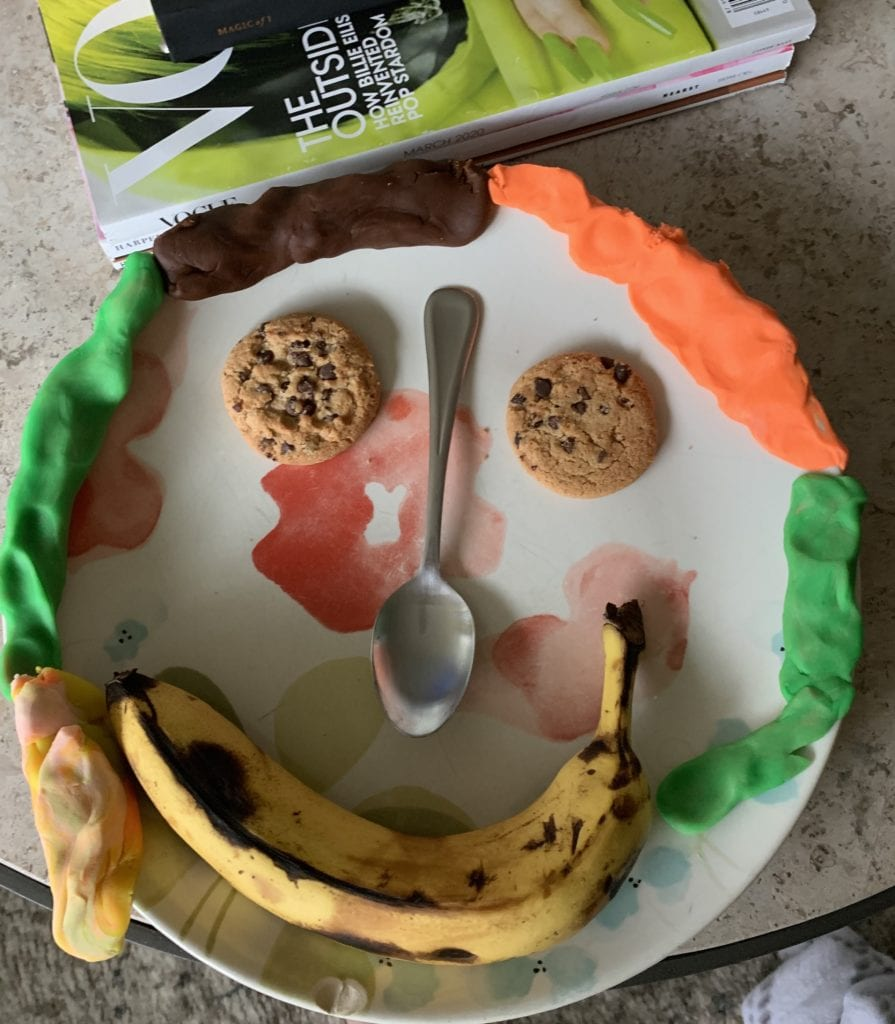 face made with a plate, cookies for eyes, a banana for a mouth, and a spoon for a nose