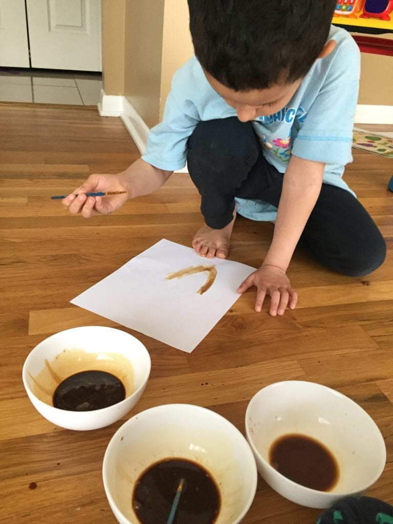 boy painting with coffee watered down on white paper