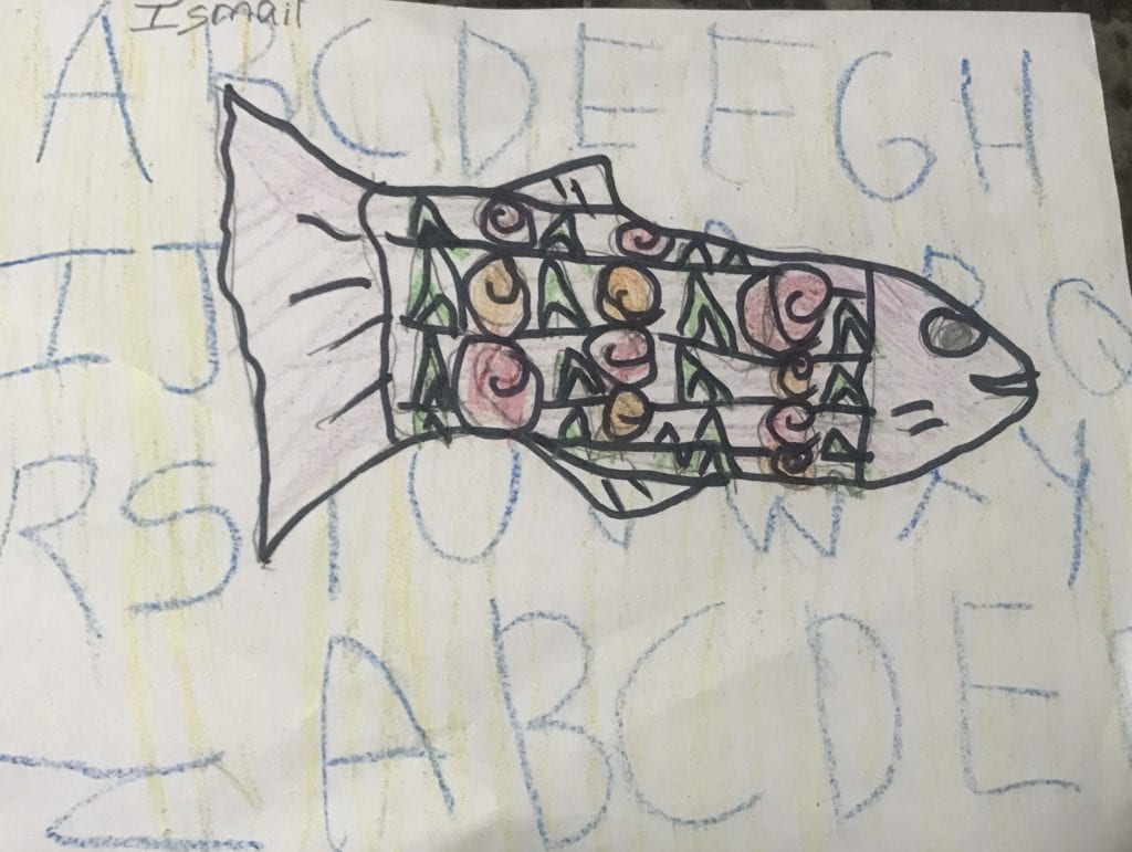 fish drawing with shape sin a pattern inside of the body and the alphabet written in the background