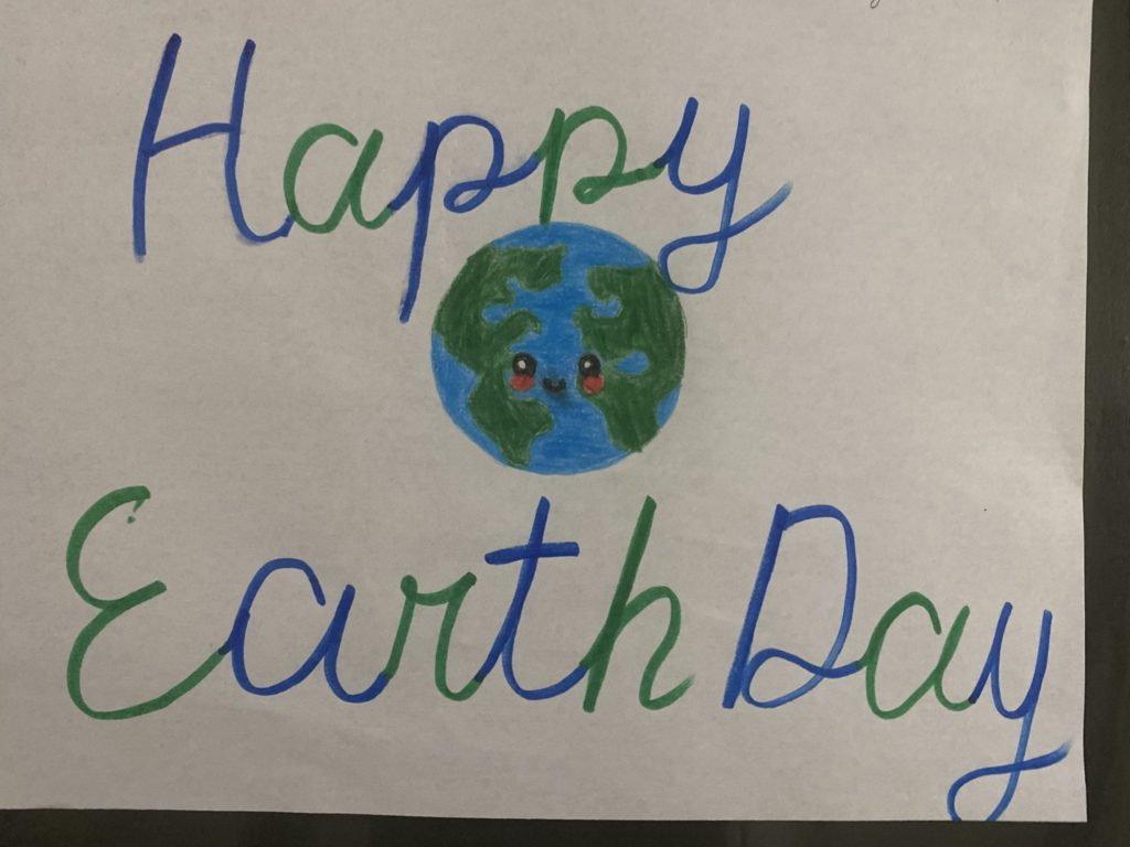 drawing that says happy earth day and has a smiling earth in the center