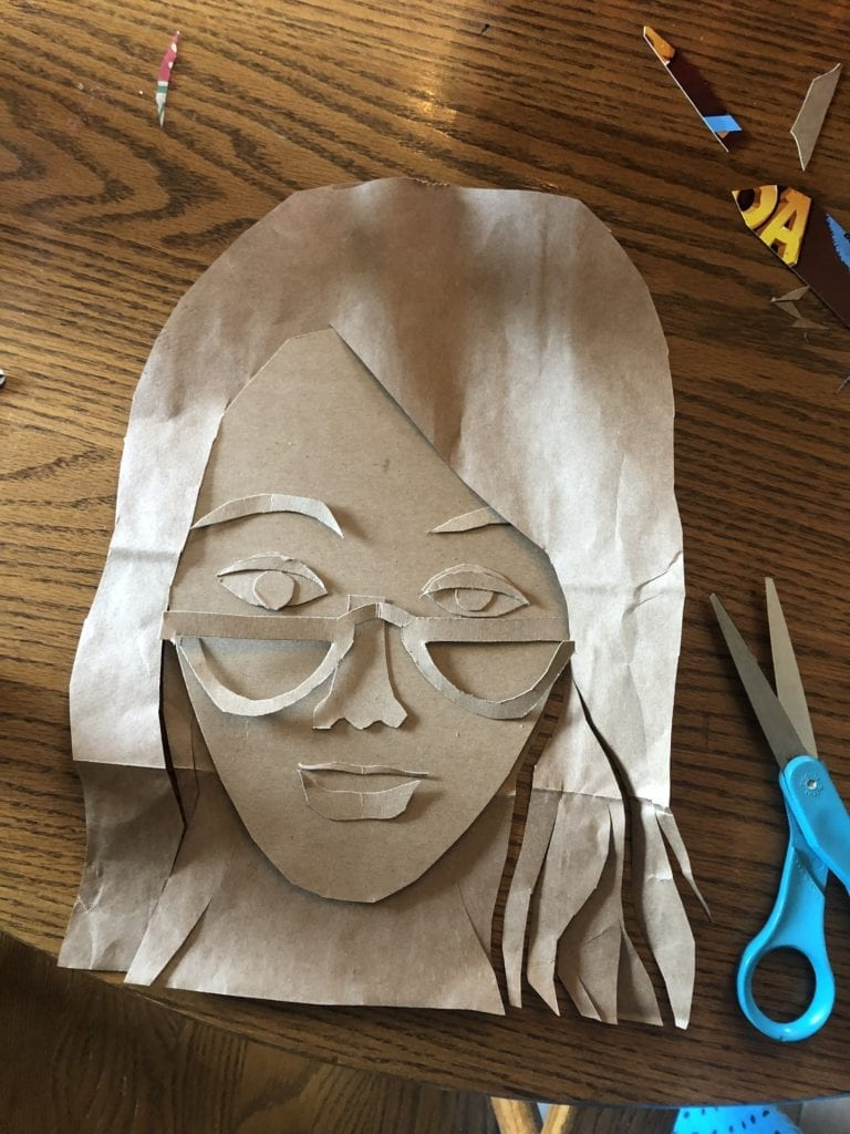 portrait that has hair, glasses, and a face made from light brown cardboard