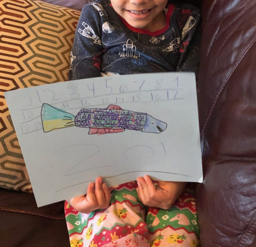 girl holding colorful fish drawing