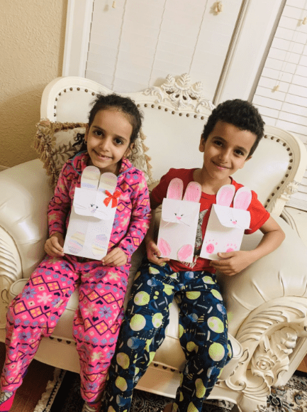 A boy and a girl sitting next to each other in a chair both holding white paper rabbits that have faces, ears, and feet colored with crayons