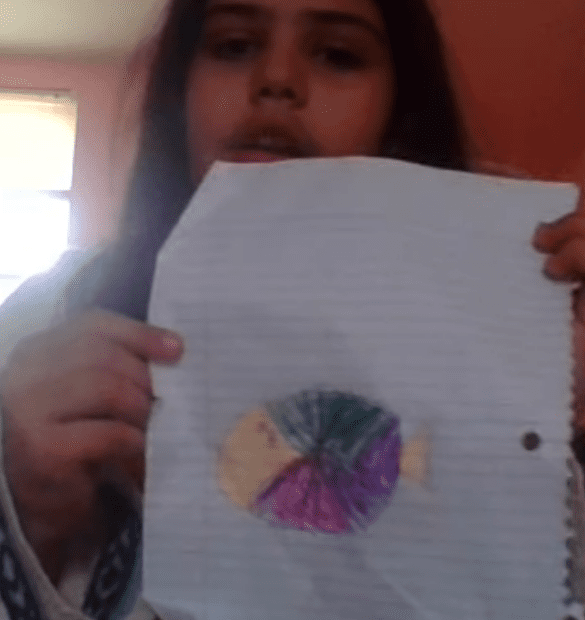girl holding a paper with a fish drawing on it