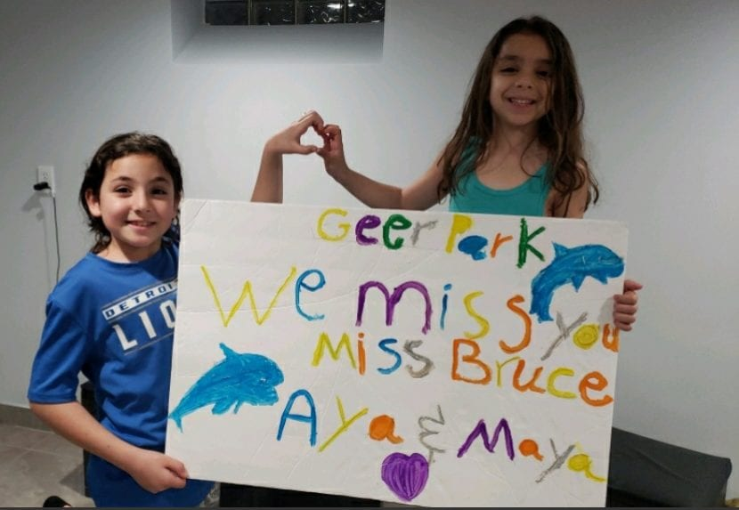 """two girls holding a hand painted sign that reads """"Geer Park, we miss you miss bruce love aya and maya"""""""