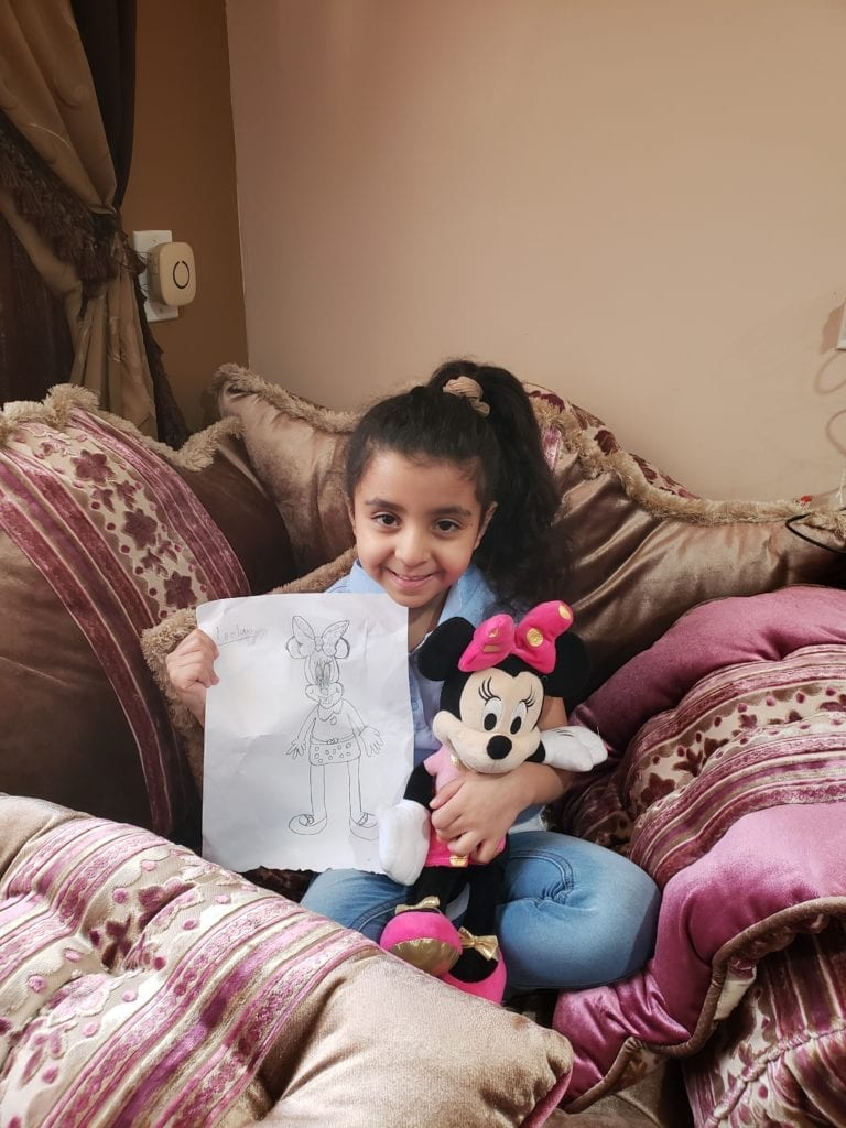 girl holding a minnie mouse stuffed animal and a drawing of minnie mouse