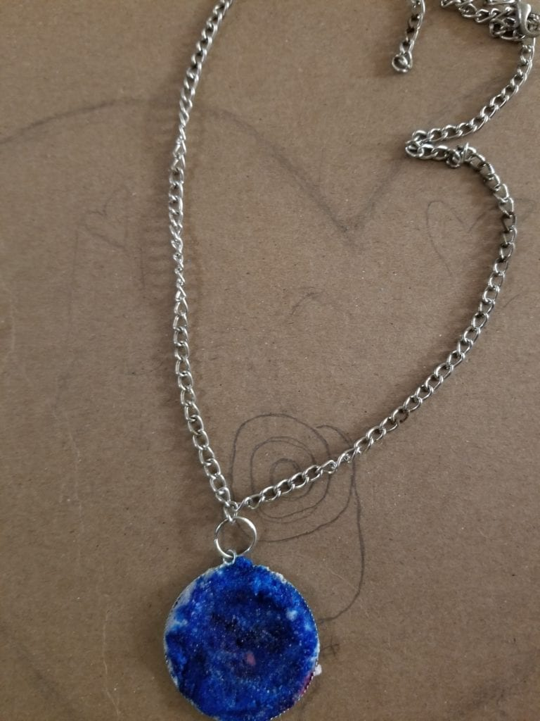 necklace with a blue medallion at the end