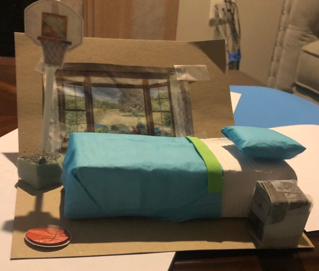 a mini 3-d room model what shows a window on the wall, a blue bed and pillow, a basketball hoop, an a nightstand