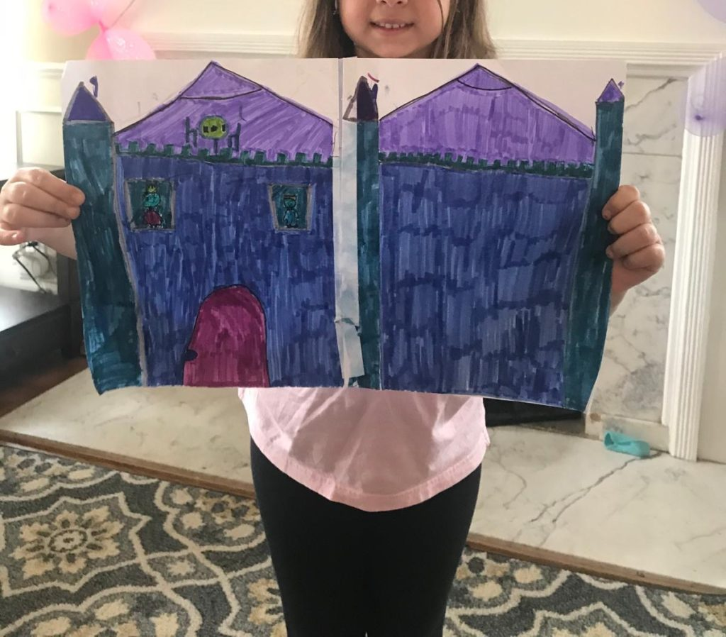 girl holding a large cool colored castle drawing
