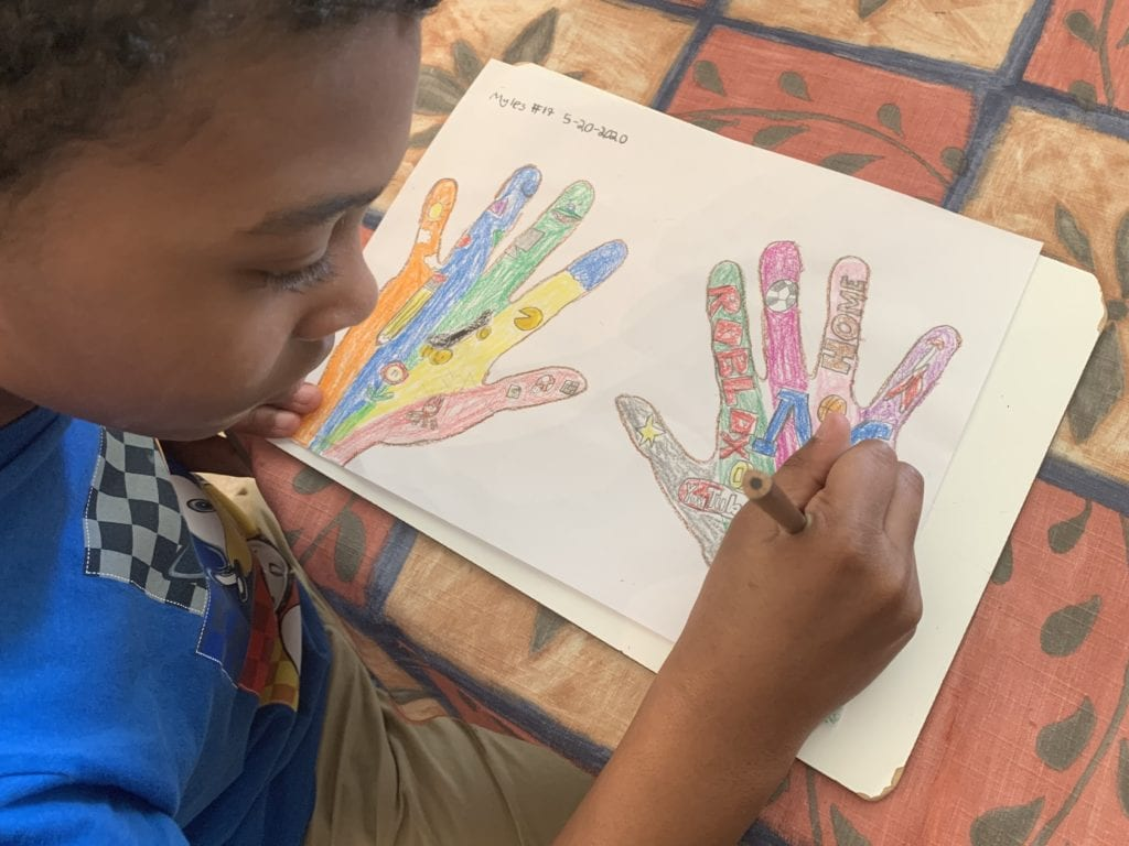 boy coloring a picture of two colorful hands