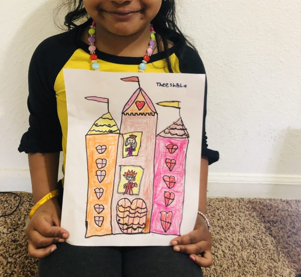 girl holding a warm colored castle drawing