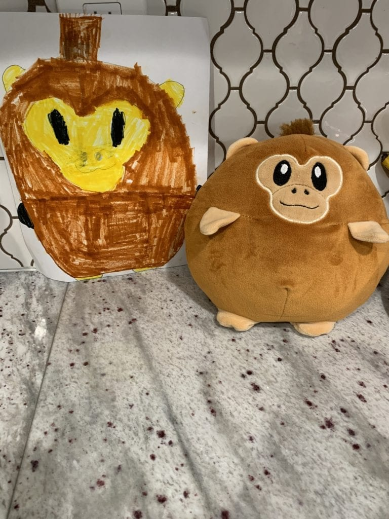 monkey stuffed animal next to a drawing of the stuffed animal
