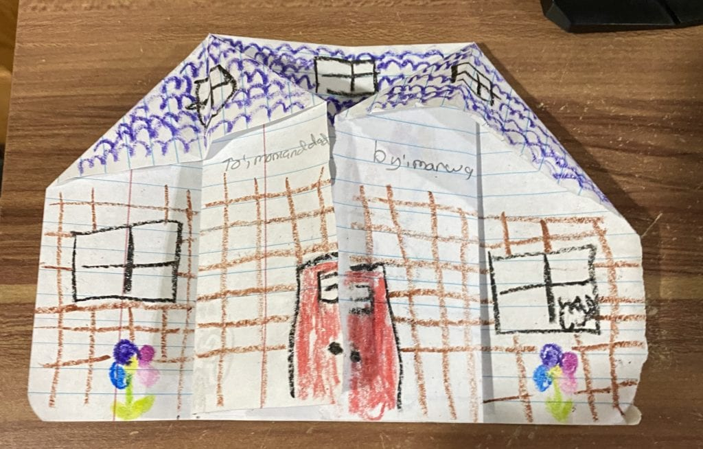 front of an origami house with drawn-n windoes, door, brick lines, and flowers