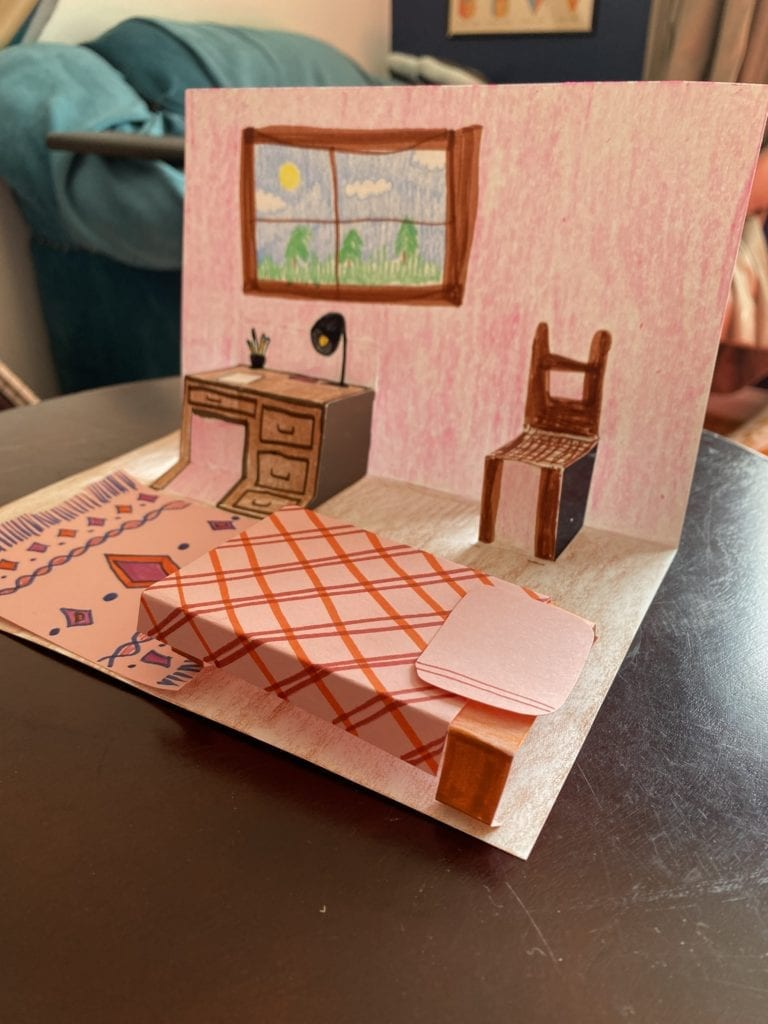 paper folded in half and pieces cut from the center and popped forwar to make them pop out, drawings make it look like a bedroom with a bed, desk, chair, rug and window