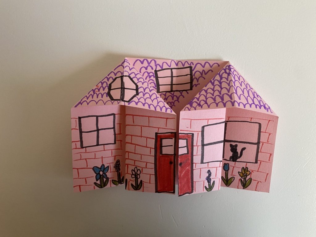 Origami house folded from pink paper; there are marker details drawn on the house including a door, windows, roof shingles, bricks, and flowers