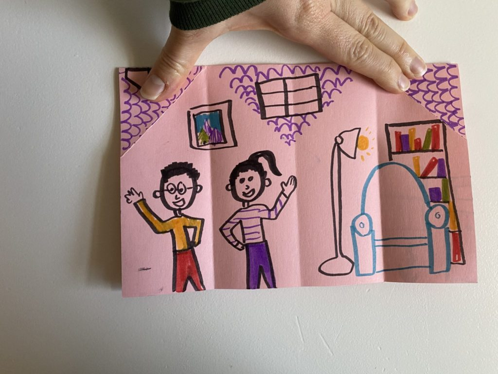 inside of an origami house showing two people waving, a chair, lamp, and bookcase drawn with marker