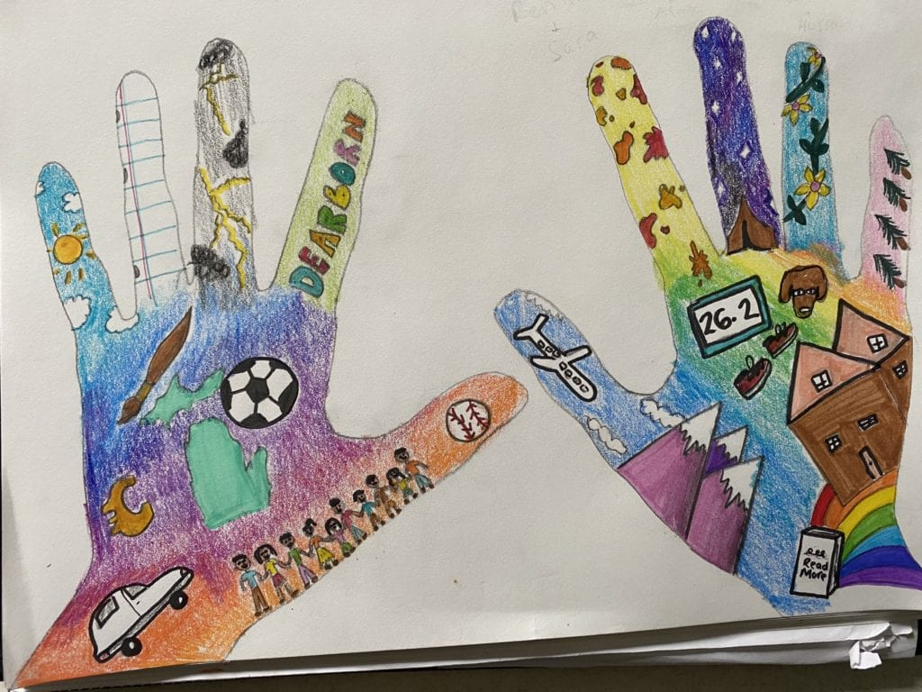 drawing of two hands colored with many different colors and are filled with drawings of things like a soccer ball, a family, a house, mountains, a dog, shoes, a car, and a map of Michigan.