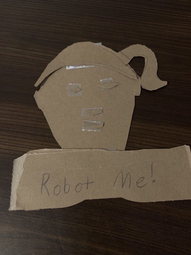 """person's face made out of cardboard that says """"Robot Me!"""""""