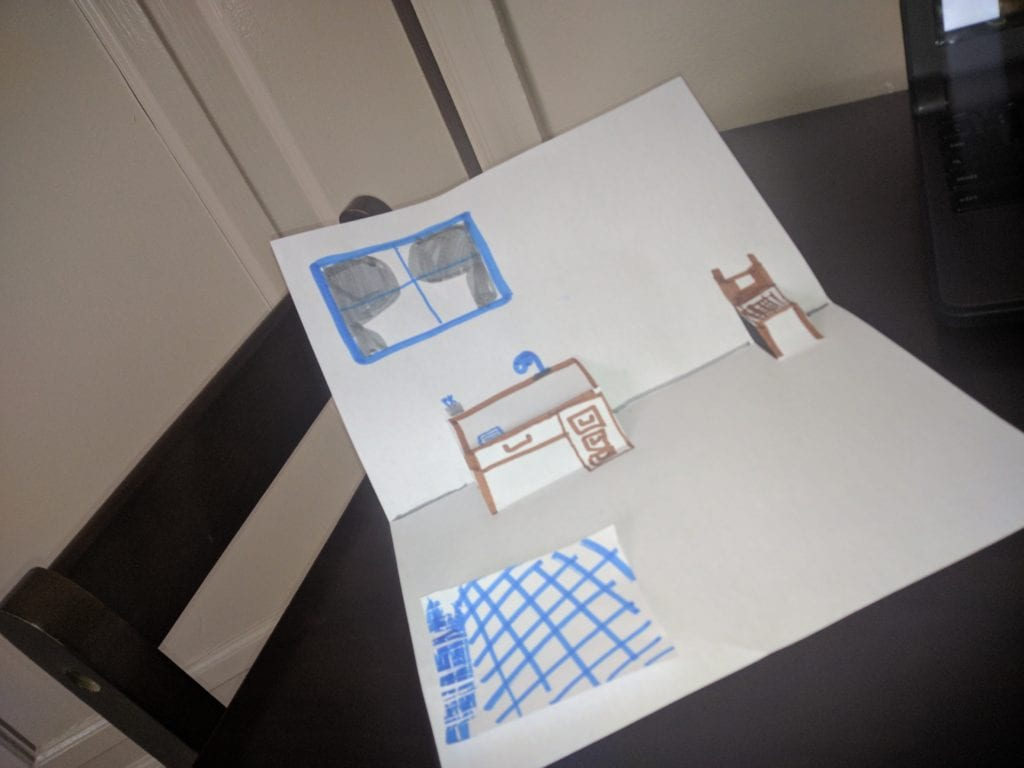 folded paper that is drawn to look like the inside of a room with a chair and desk that pop out, a window and rug drawn