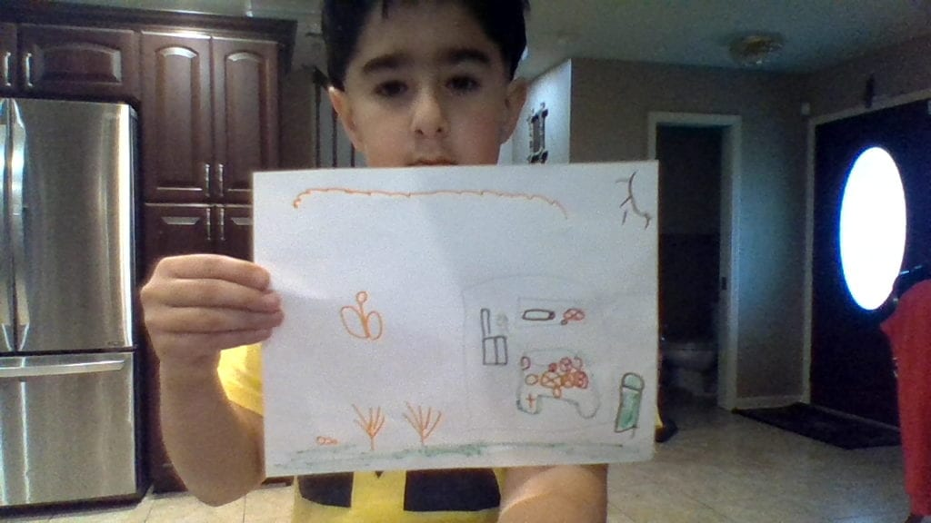 boy holding a drawing of a house outside