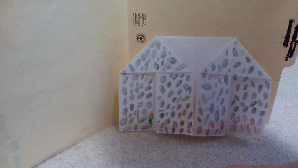 origami house with stones drawn in pencil on the outside of it