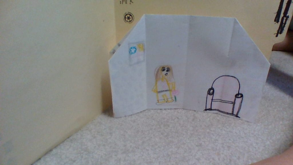 inside of an origami house with a person, a chair, and a window