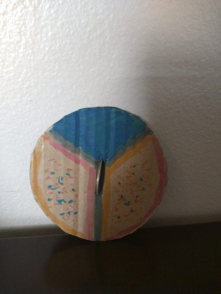 cardboard circle colored and a coin is placed in the middle to make a top spinner
