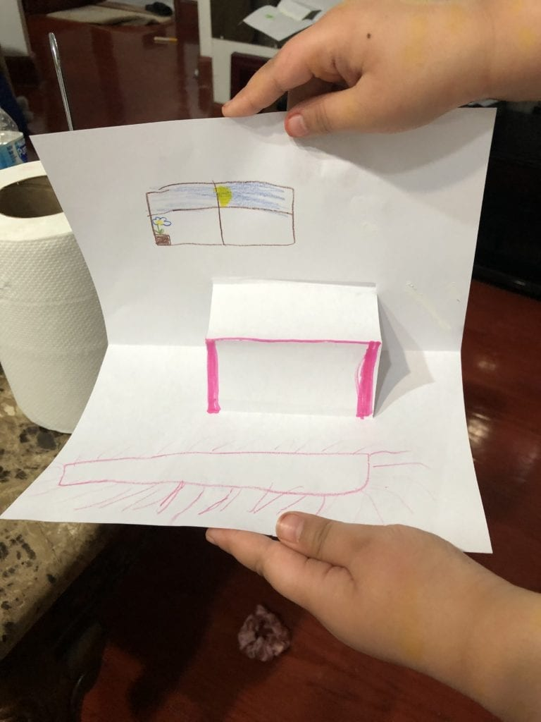 pop up table made from paper with a window and rug drawn on the paper