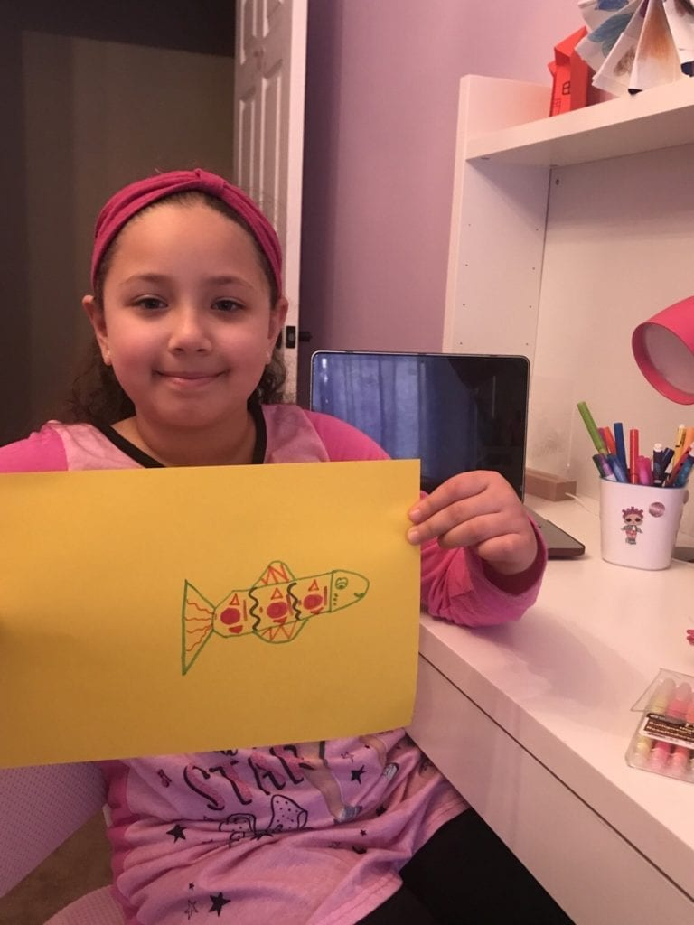 girl holding a fish drawing filled with patterns