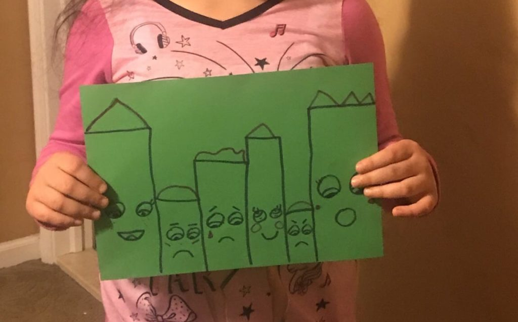 girl holding a drawing of a city that has buildings with faces