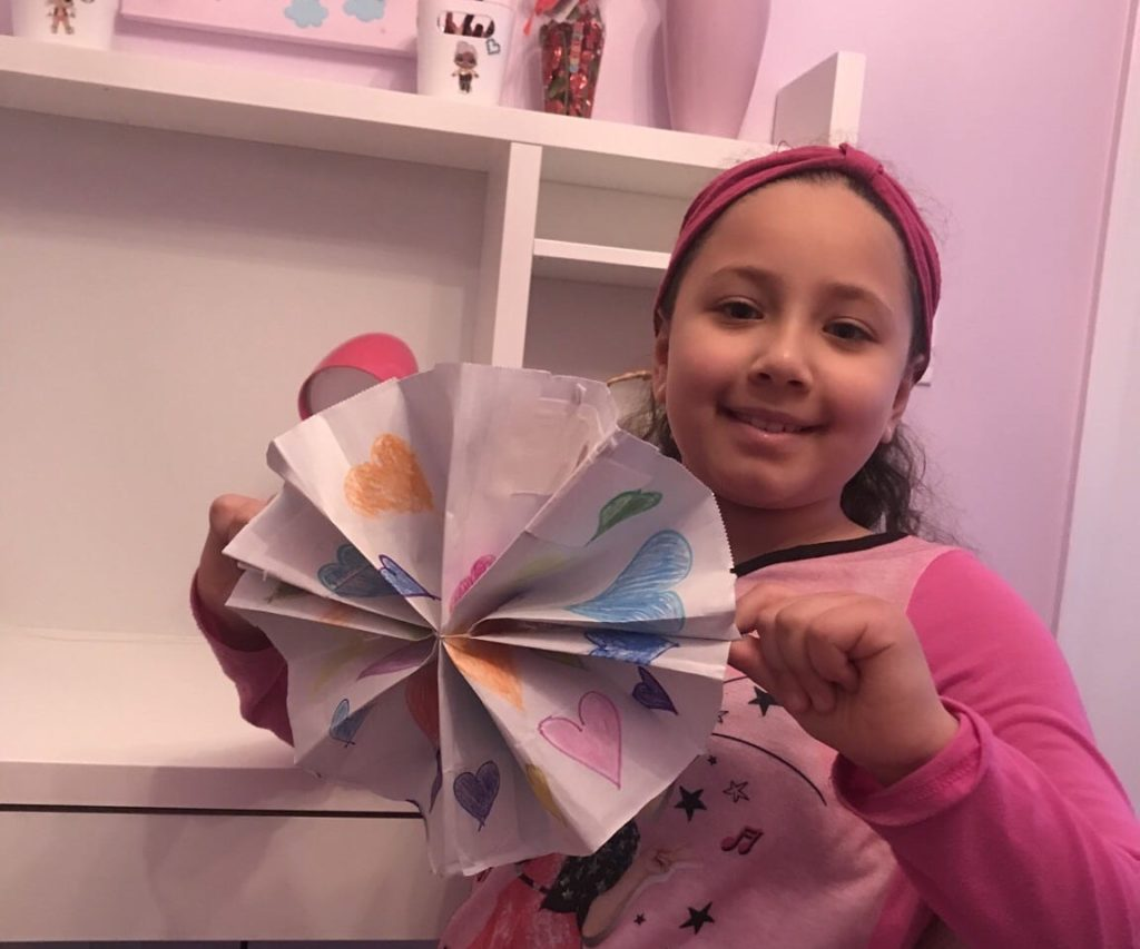 girl holding a paper folded fan with hearts on it
