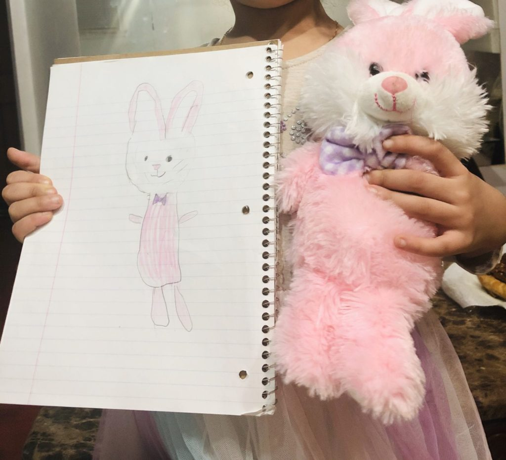 girl holding a pink stuffed rabbit and a drawing of the rabbit