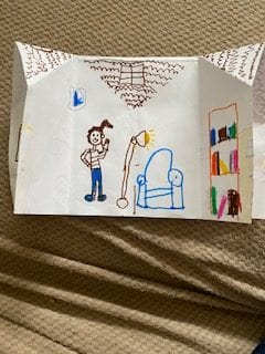 inside of an origami house with a person and furniture drawn with marker