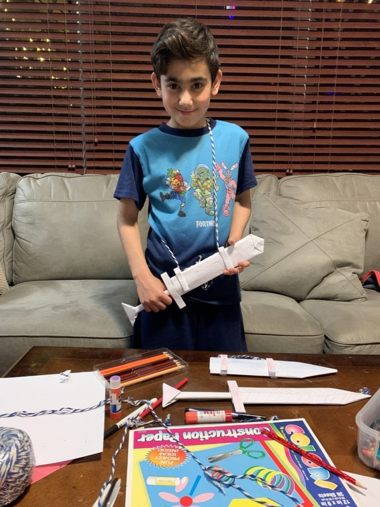 boy holding paper sword he made
