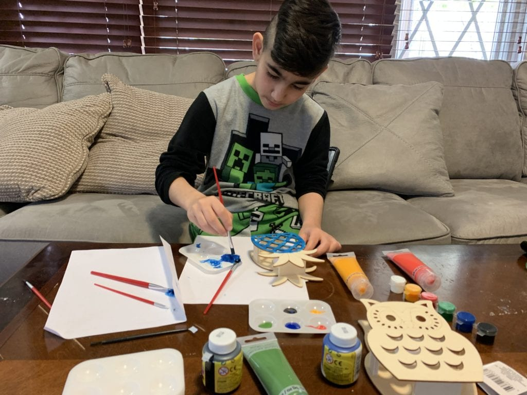 boy painting a wooden pineapple
