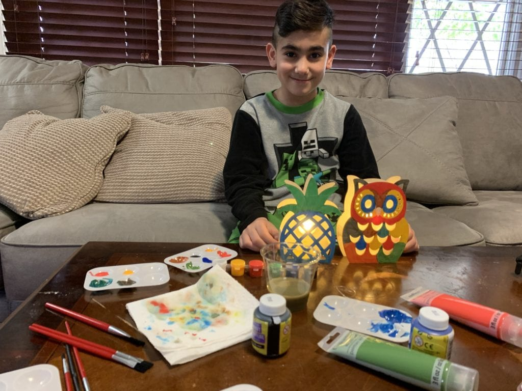 boy showing his wooden pineapple lamp and owl lamp