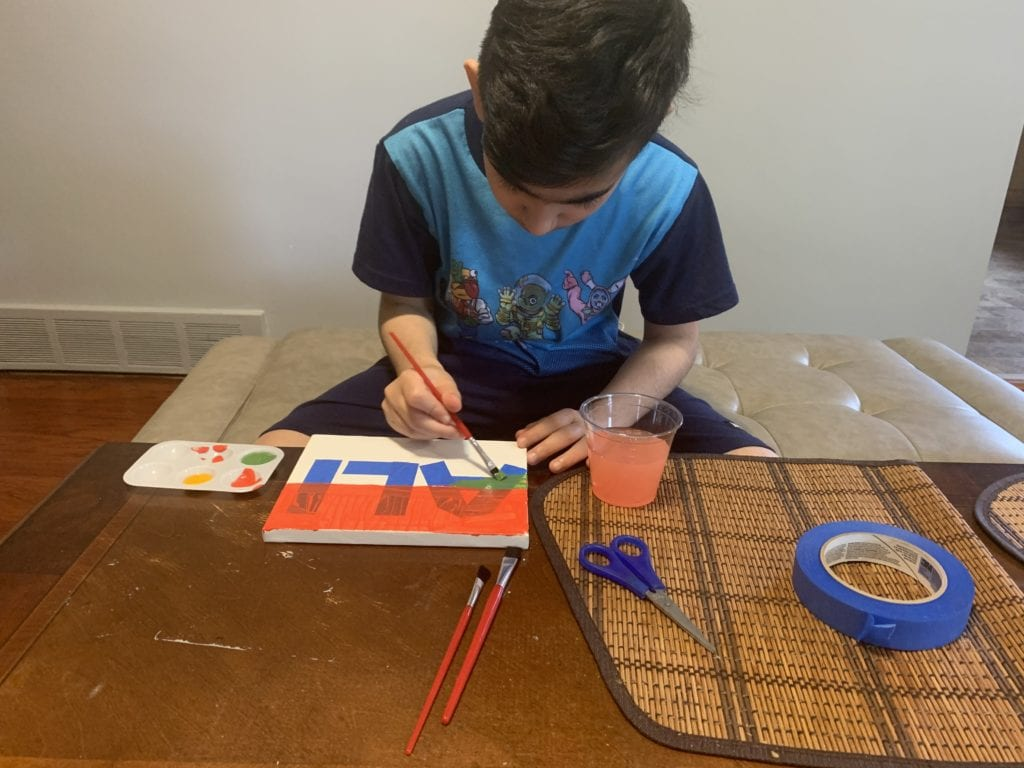 boy painting a sign
