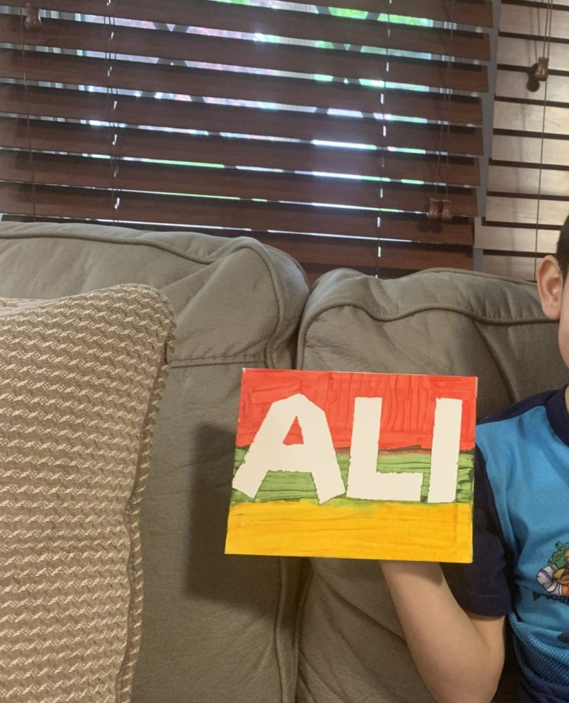boy holding a painted sign that says ALI