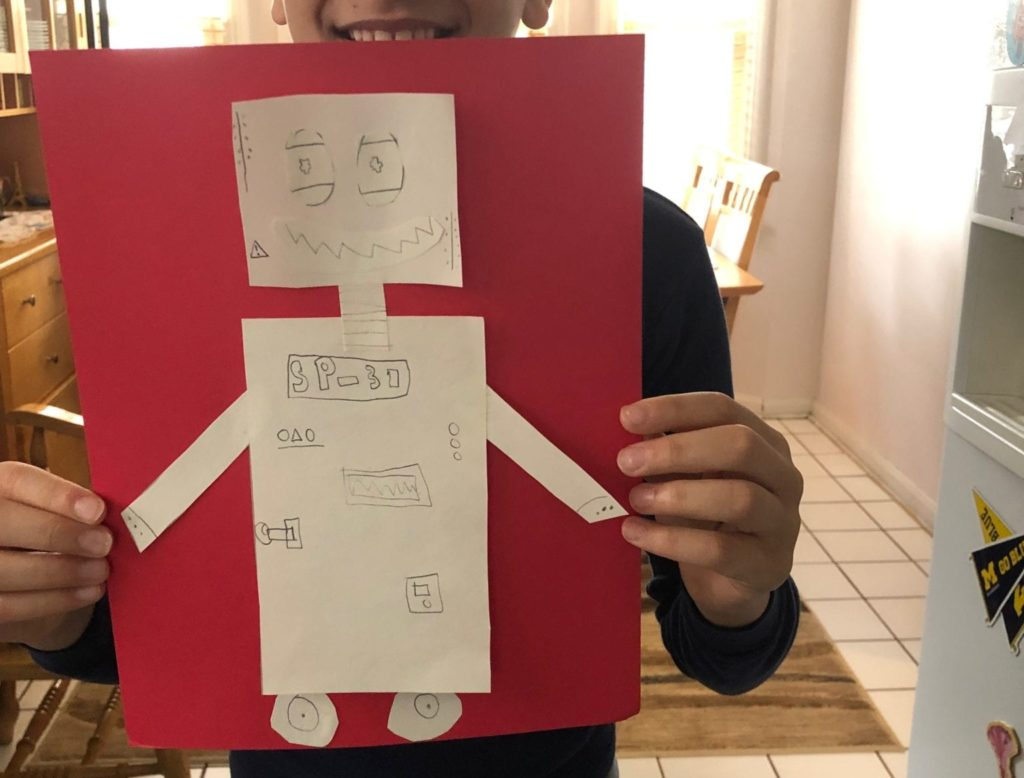 robot drawn on whte paper with a pencil and then glued to red paper