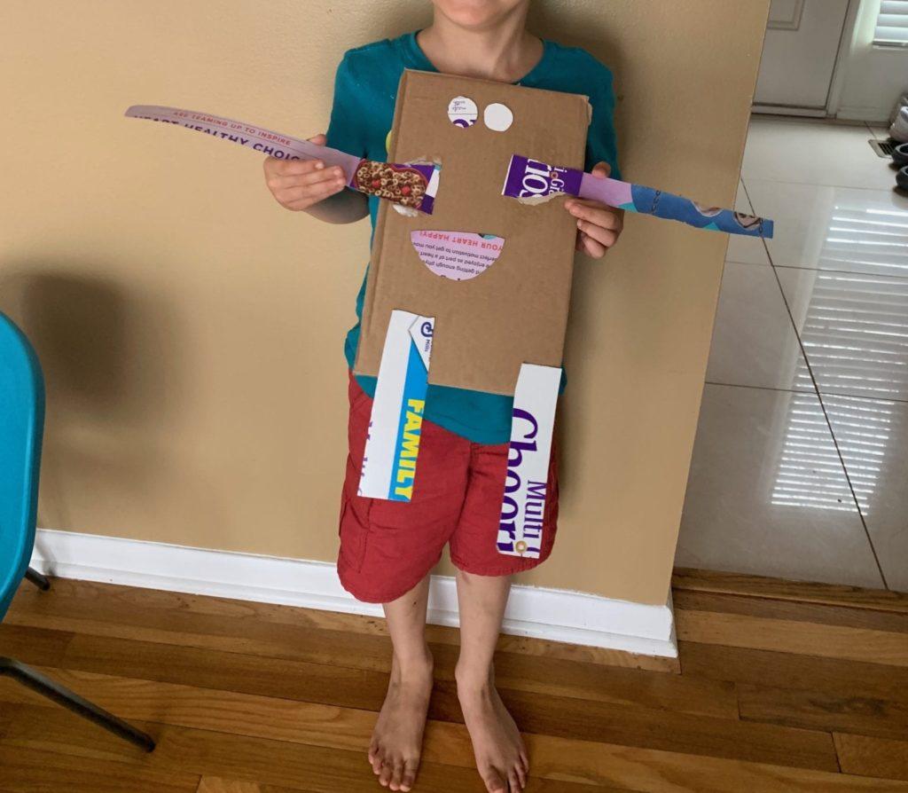 boy holding a cardboard robot
