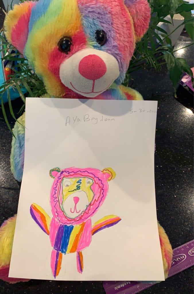 drawing of a rainbow teddy bear in front of a real rainbow teddy bear